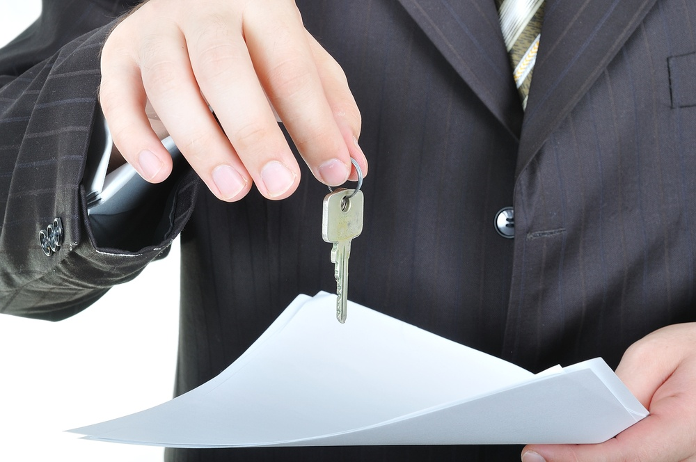 One businessman hand and the key, paper agreement